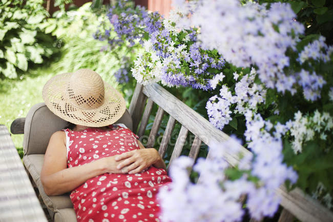Женщина лежит на скамейке в саду — стоковое фото