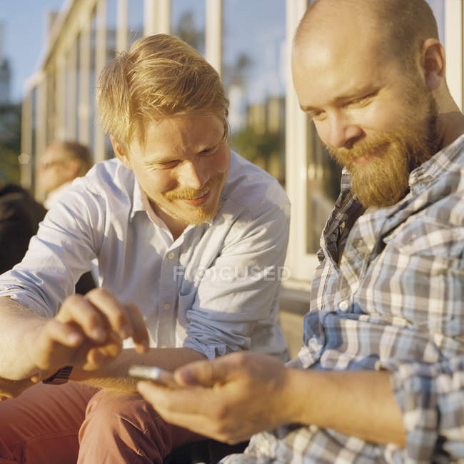 Two men using mobile phone, differential focus — Stock Photo