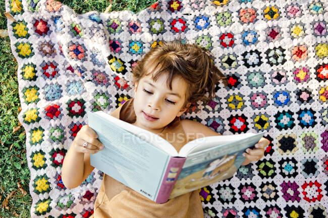 Дівчина читає книжку на пікніковому покритті. — стокове фото