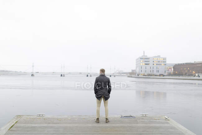 Man standing by waterfront, back view — Stock Photo