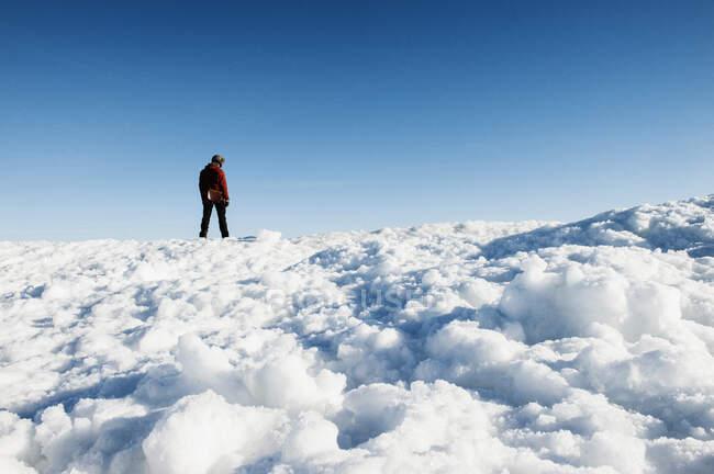 Uomo in piedi sulla montagna innevata — Foto stock
