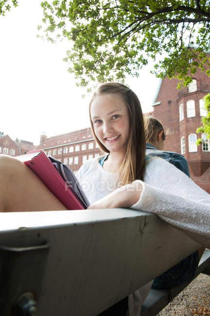 Adolescente che si siede sulla panchina e studiare — Foto stock