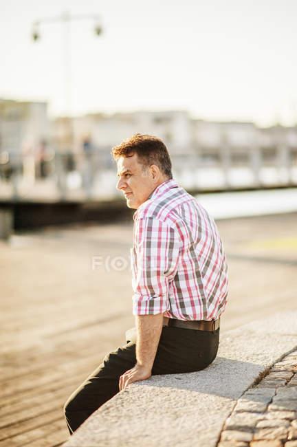 Homme d'âge mûr assis sur le rebord et la recherche. — Photo de stock