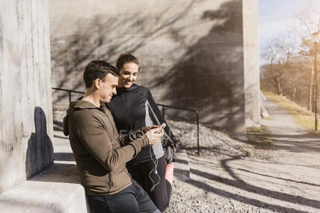 Пара стоїть і користується розумним телефоном. — стокове фото