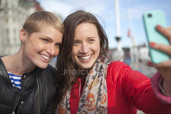 Две женщины делают селфи на смартфоне, фокусируются на переднем плане — стоковое фото