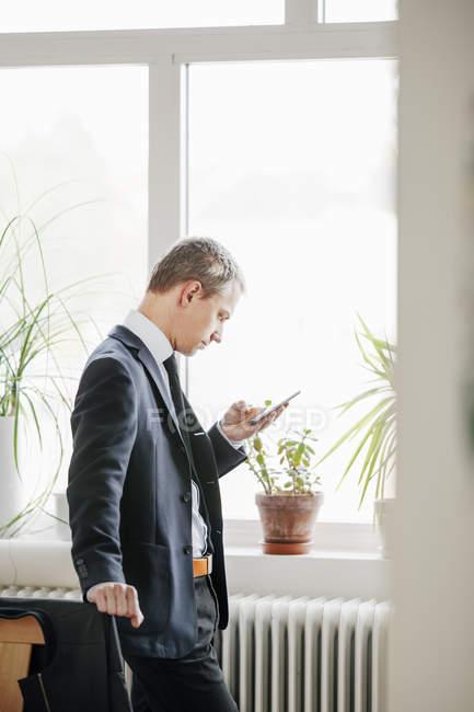 Uomo d'affari adulto metà utilizzando smart phone — Foto stock