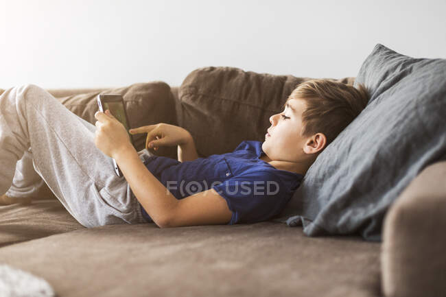 Boy on sofa playing with tablet PC — Stock Photo