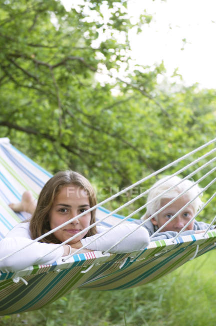 Girl and boy lying on striped hammock, selective focus — Stock Photo