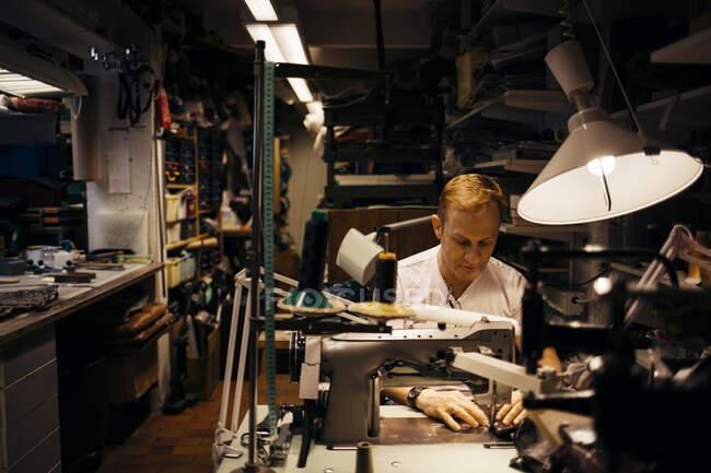 Мужчина зрелого возраста с волосами работает в кожевенной мастерской — стоковое фото