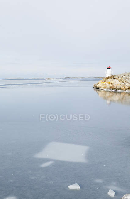Lighthouse by frozen sea, northern europe — Stock Photo