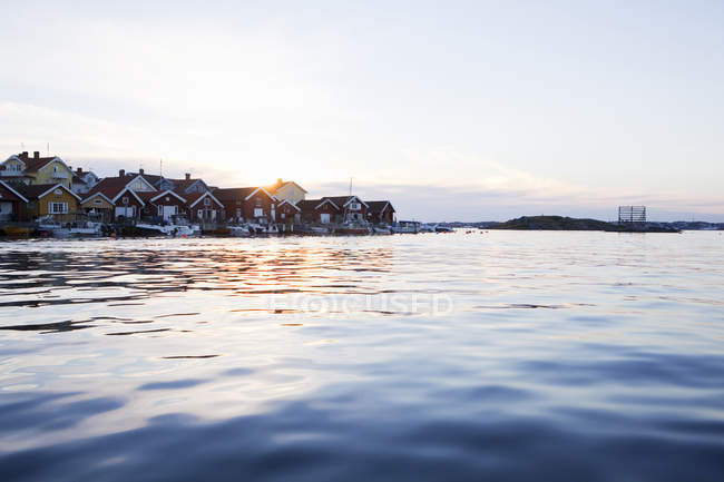 Houses and motorboats by sea at sunset, differential focus — Stock Photo