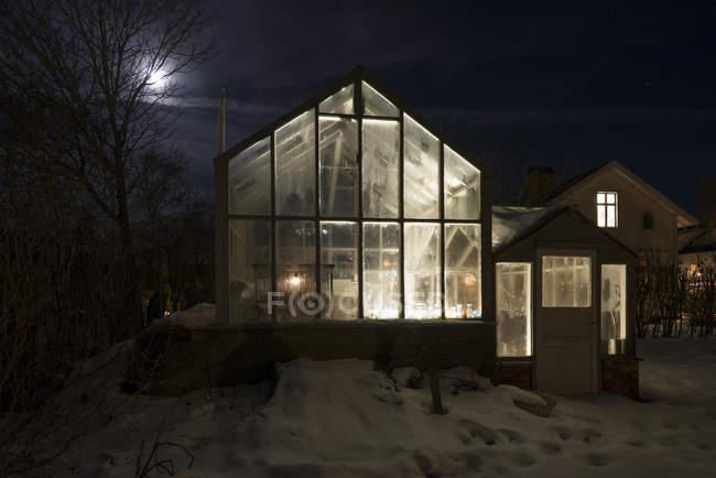 Exterior of illuminated greenhouse at night, northern europe — Stock Photo