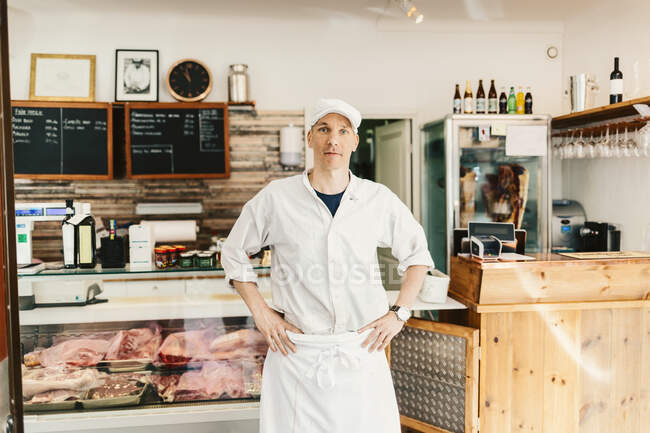 Portrait of butcher standing and looking at camera in store — Stock Photo