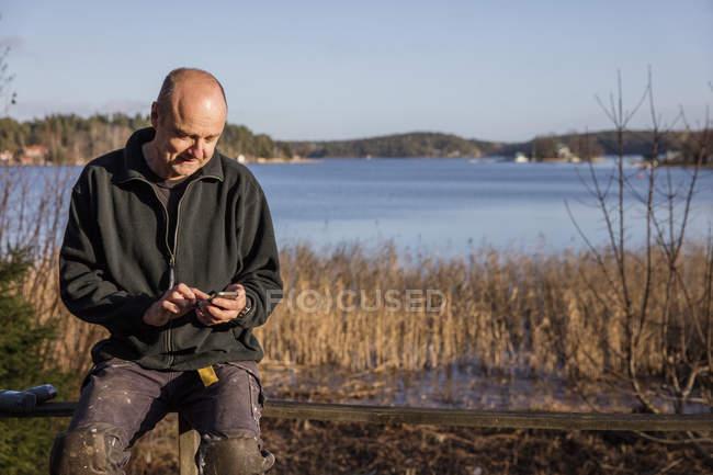 Человек сидел на скамейке и использование смарт-телефон — стоковое фото
