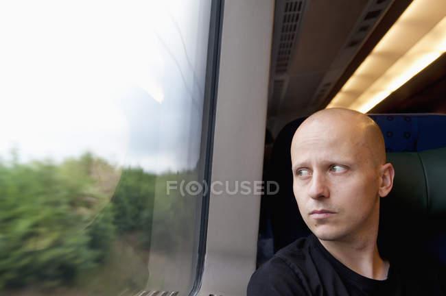Homme regardant par la fenêtre du train — Photo de stock