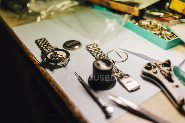 Wristwatch parts on desk, focus on foreground — Stock Photo