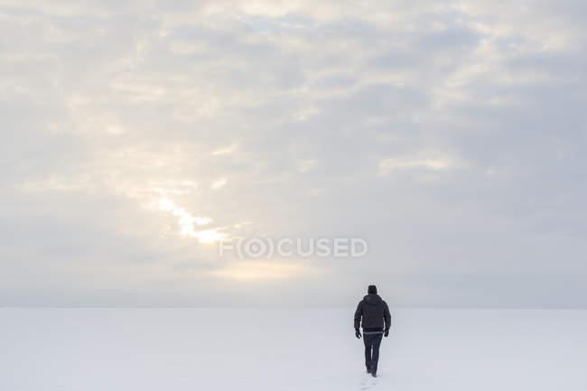 Vista posteriore dell'uomo maturo che cammina sulla neve — Foto stock