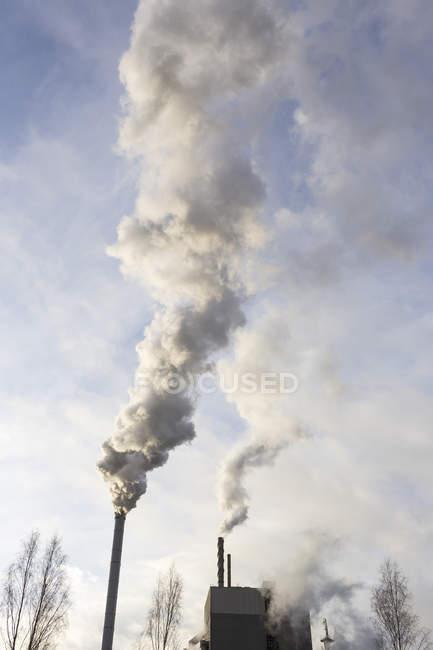 Vista de ángulo bajo de humo procedente de las pilas de humo - foto de stock