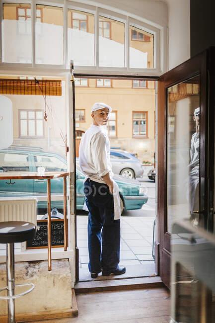 Butcher at doorway of butcher shop — Stock Photo