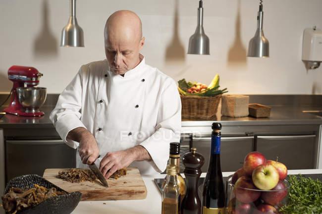 Шеф-кухар дивиться і подрібнення їжі на кухні — стокове фото