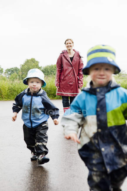 Mother and children walking on wet road — Stockfoto