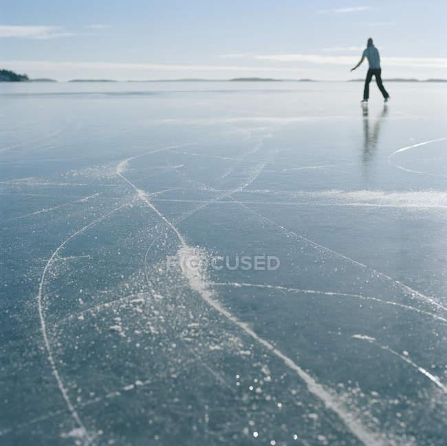 Mitte erwachsene Eisläuferin auf zugefrorenem See — Stockfoto