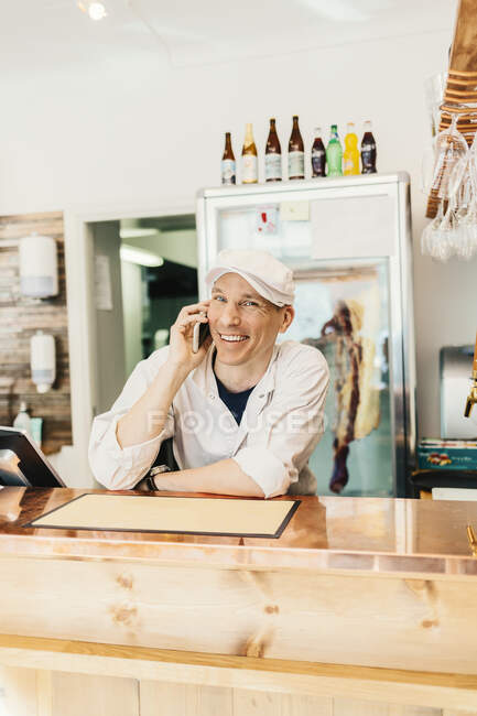 Butcher talking on phone at butcher shop — Stock Photo