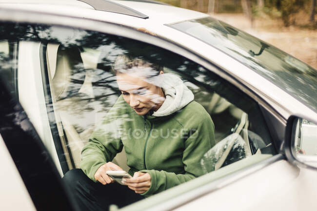 Young woman sitting in car on smart phone — Stock Photo