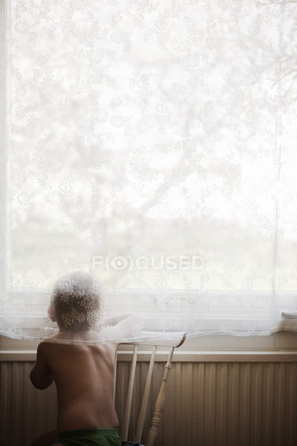 Rückansicht des Jungen, der durch das Fenster schaut — Stockfoto