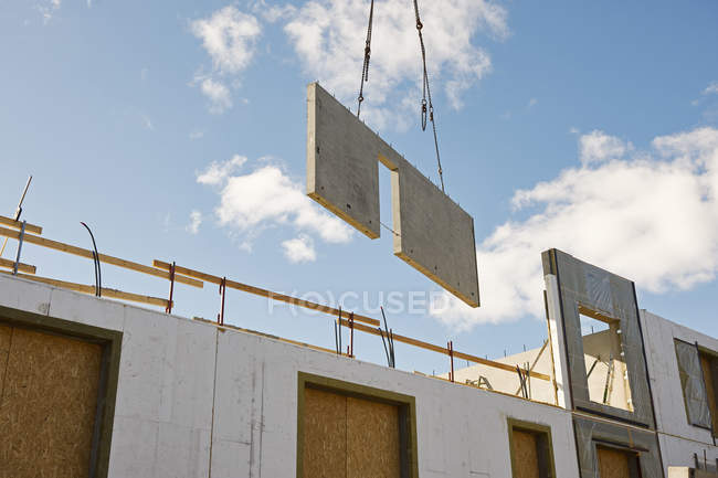 Industrial cranes lifting wall on construction site — Stock Photo