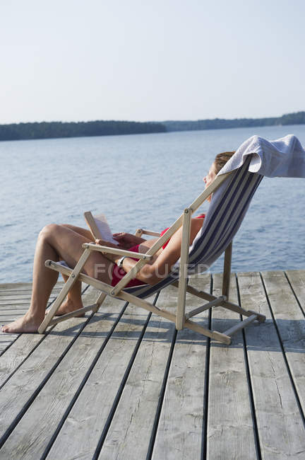 Mature woman sunbathing in deckchair near sea — Stock Photo