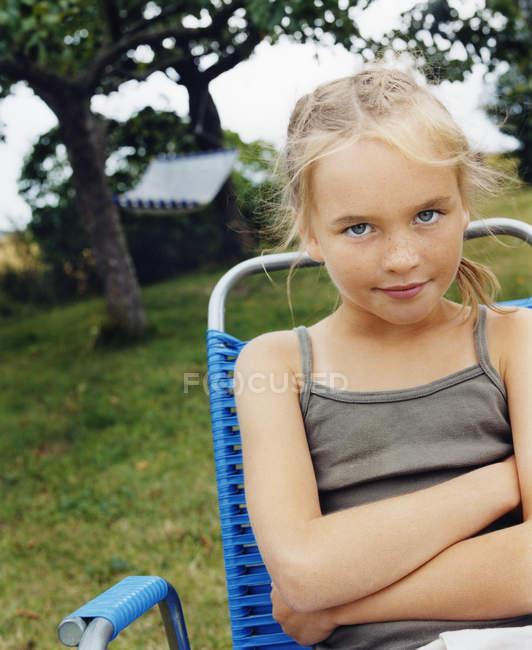 Jeune fille blonde, assis dans la chaise pliante de jardin — Photo de stock