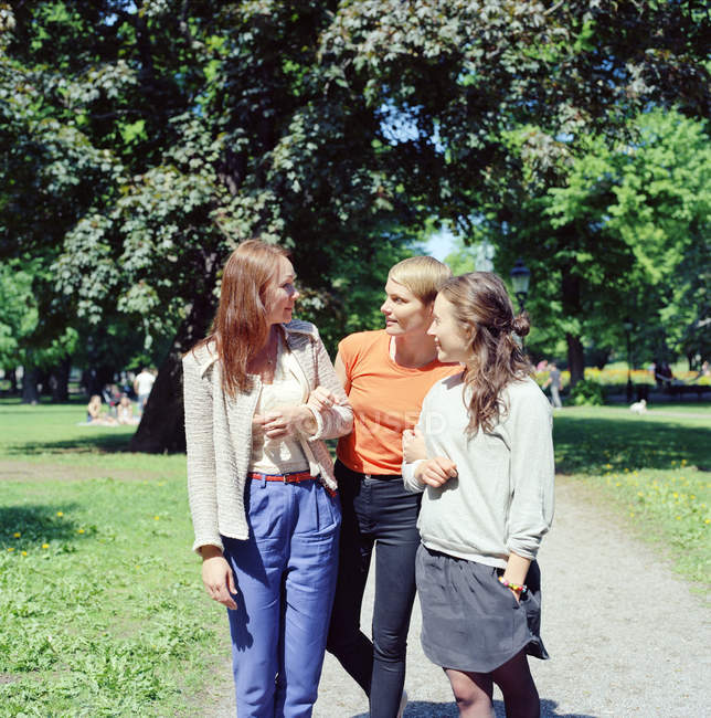 Three young women walking through park — Stock Photo