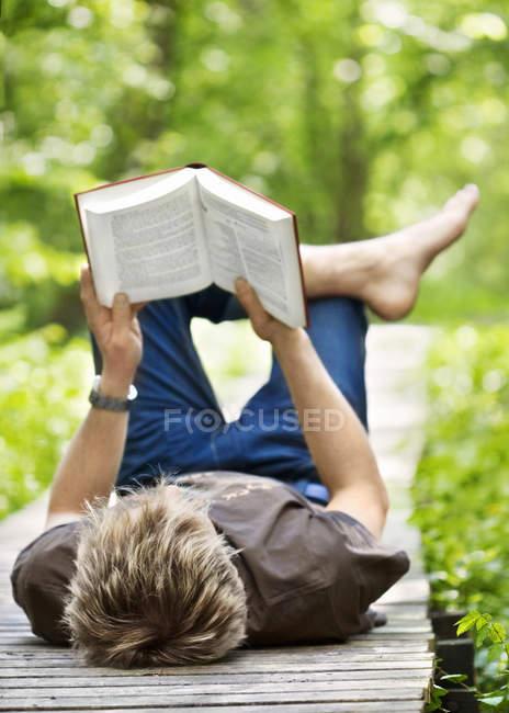 Молодой человек лежит на деревянной пристани и читает книгу — стоковое фото