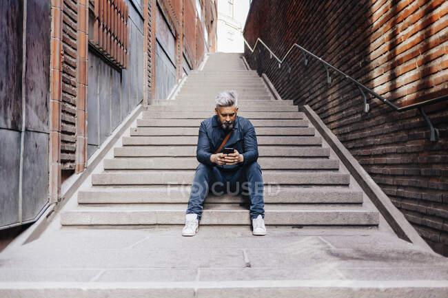 Uomo con smart phone seduto su scala — Foto stock