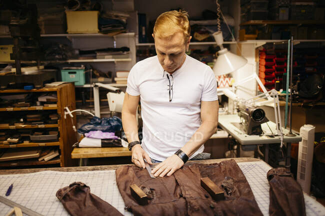 Focused mature man working in leather workshop — Stock Photo