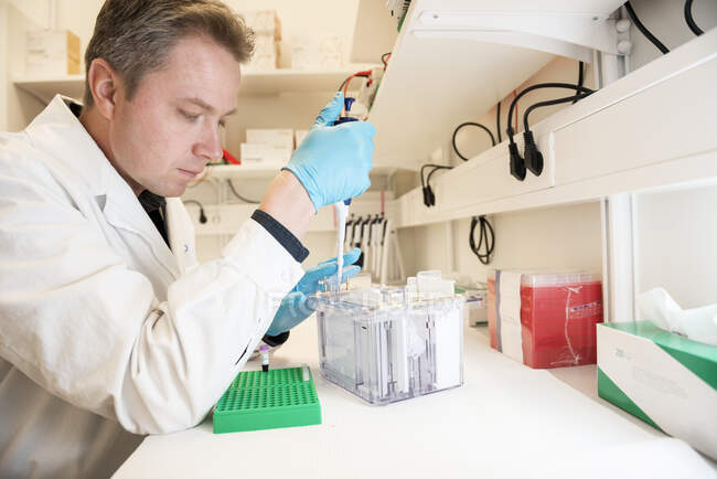 Man in white coat working in lab — Stock Photo