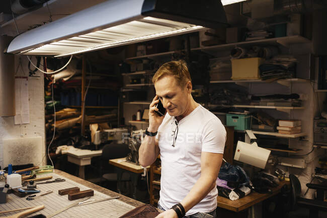 Mature man with blond hair working in leather workshop — Stock Photo