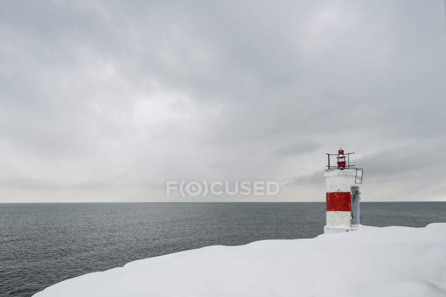 Lighthouse on snowy coastline, northern europe — Stock Photo