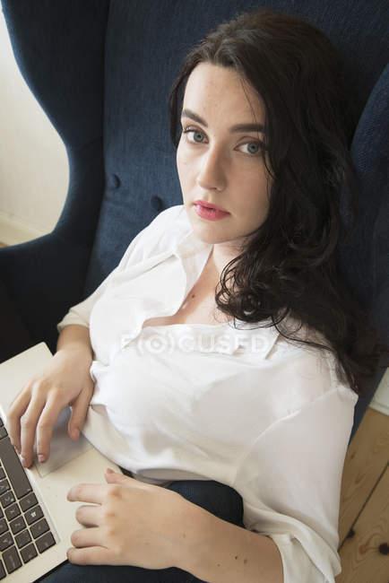 Giovane donna che utilizza il computer portatile e guardando la fotocamera — Foto stock