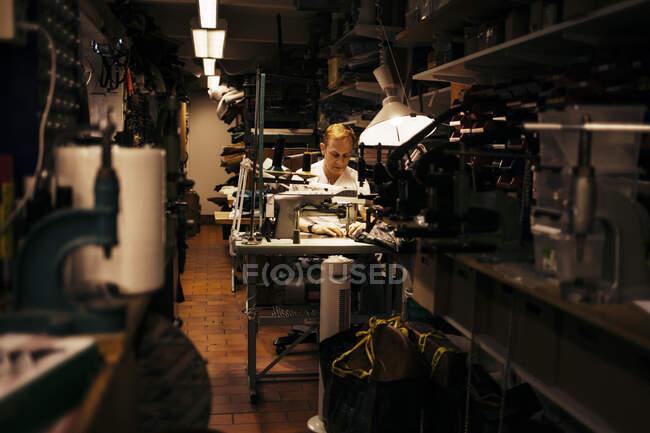 Зрілий чоловік з світлим волоссям працює в шкіряній майстерні. — стокове фото