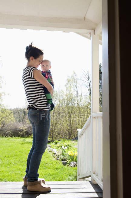 Femme portant bébé garçon, foyer sélectif — Photo de stock