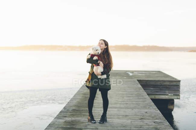 Молодая женщина на пире с собакой зимой — стоковое фото