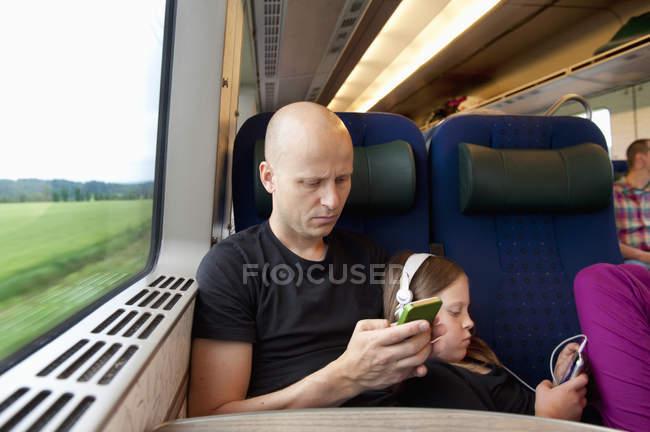 Pai e filha, através de telefones celulares no trem — Fotografia de Stock