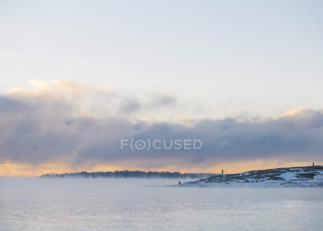 Foggy coastal landscape with incidental people in background — Stock Photo