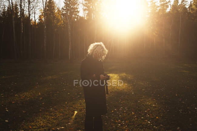 Mid adult woman standing in sunlight — Stock Photo
