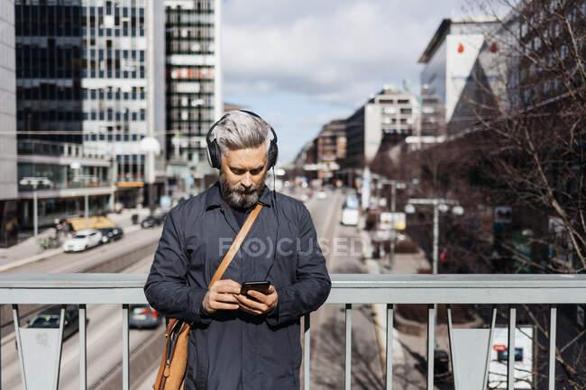 Homem em telefone inteligente na rua em Estocolmo, Suécia — Fotografia de Stock