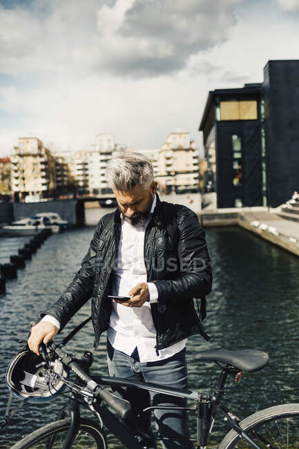 Man on smart phone with bicycle in Stockholm, Sweden — Stock Photo