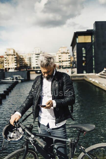 Uomo su smart phone con bicicletta a Stoccolma, Svezia — Foto stock