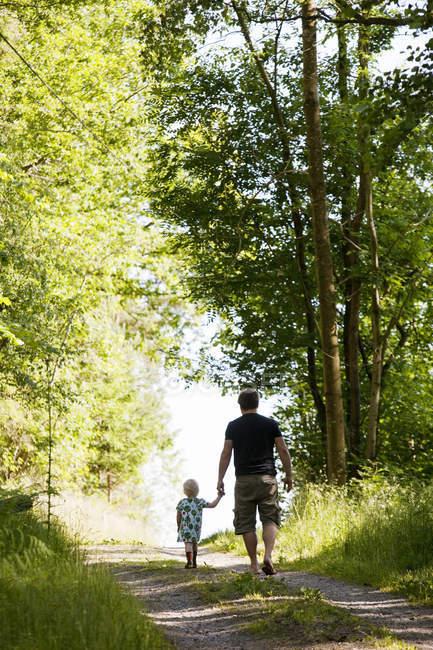 Pai e filha que andam através da floresta — Fotografia de Stock